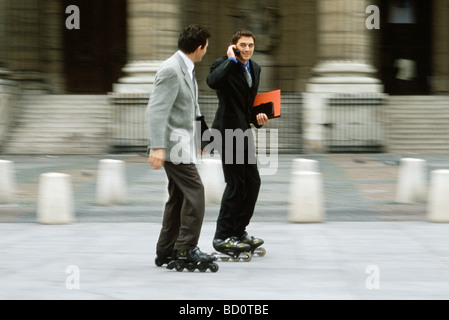 Men in business attire inline skating together along sidewalk, one phoning - Stock Photo