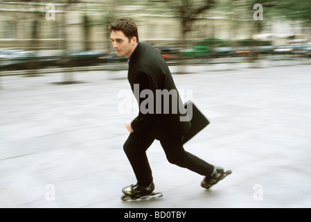 Man in business attire inline skating carrying briefcase in city square - Stock Photo