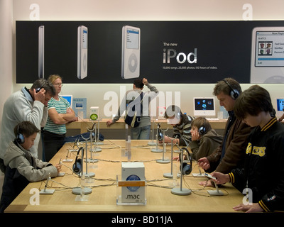 Consumers people testing listening to iPods in the Apple Store in Regent Street London UK - Stock Photo