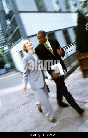 Businessman and businesswoman walking together in conversation, woman laughing - Stock Photo
