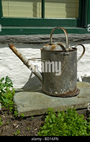 Old zinc watering can on piece of slate in garden England UK United Kingdom GB Great Britain - Stock Photo
