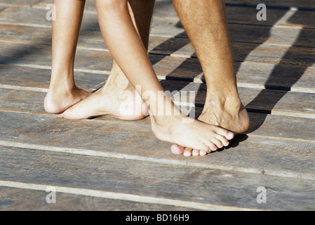 Person standing on top of another person's bare feet, cropped - Stock Photo
