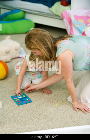 Mother and daughter playing together in child's bedroom - Stock Photo