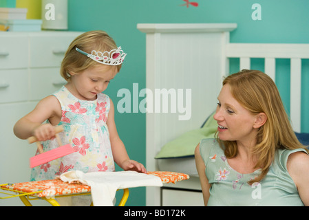 Little girl playing in bedroom with mother, pretending to iron - Stock Photo