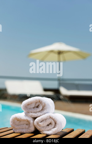 Fresh towels rolled and stacked on poolside table - Stock Photo
