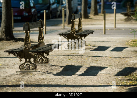 Ornate park benches casting shadows on ground - Stock Photo