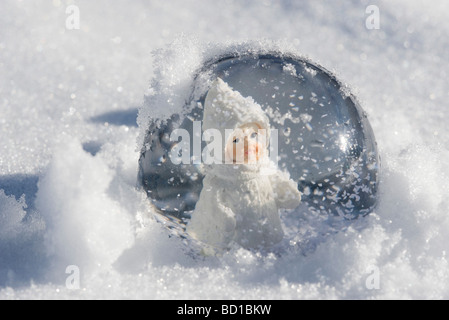 Snow globe with figurine of little girl in winter clothing sitting in snow - Stock Photo