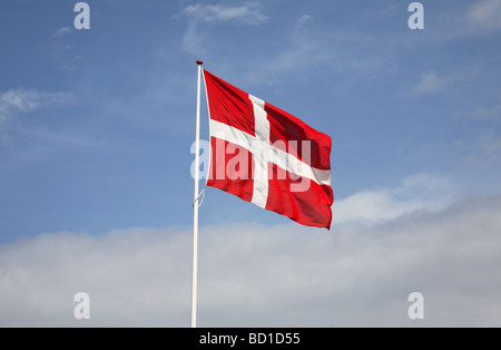 The Danish flag, the Dannebrog against white clouds and a blue sky. - Stock Photo