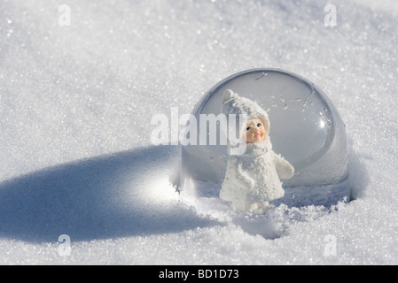 Snow globe in snow, figurine of little girl wearing winter coat and hat looking out - Stock Photo