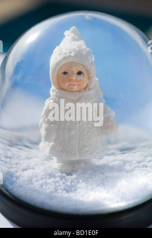 Snow globe, figurine of little girl wearing winter coat and hat looking out - Stock Photo