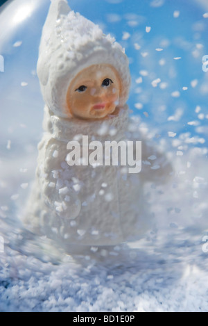 Snow globe, figurine of little girl wearing winter coat and hat looking at snow flakes falling - Stock Photo