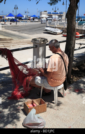 Fisherman repairing fishing nets in the harbour, Savelletr,i Puglia, Italy. - Stock Photo