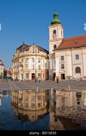 Romania's Sibiu City Hall and Holy Trinity Roman Catholic Cathedral tower on the Piata Mare Square pedestrian plaza - Stock Photo