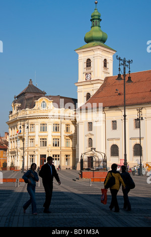 Romania's Sibiu City Hall and Holy Trinity Roman Catholic Cathedral tower on the Piata Mare Square pedestrian plaza - Stock Photo