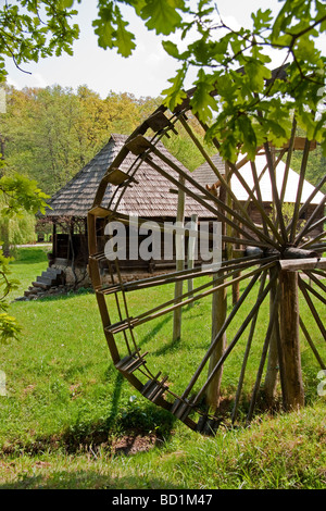 Romania's Museum of Traditional Folk Civilization water wheel and dwellings at Sibiu in Transylvania - Stock Photo