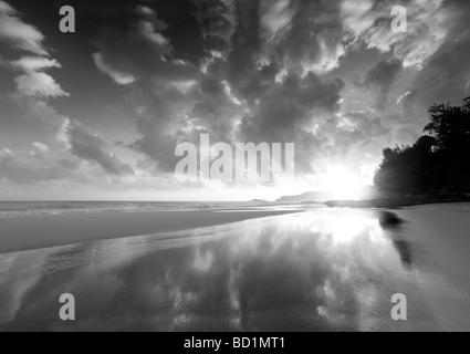 Sunrise at low tide at Secret Beach Kauai Hawaii - Stock Photo