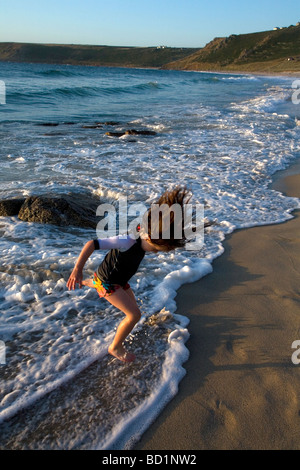 Young girl enjoying playing at jumping over gentle waves rolling on the beach. Good fun and memories of childhood - Stock Photo