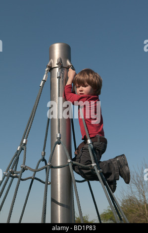 three year old boy in playground on rotating climbing frame - Stock Photo