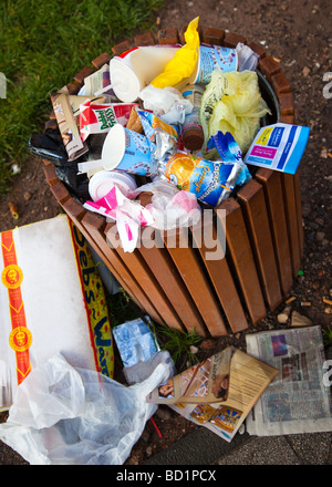Litter bin overflowing in the street - Stock Photo