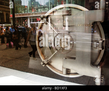 Silver bank vault door with reflection street in glass exhibition. - Stock Photo