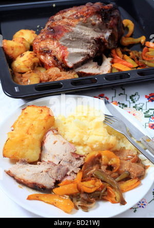 A meal of roast pork with the joint and roasted vegetables behind - Stock Photo