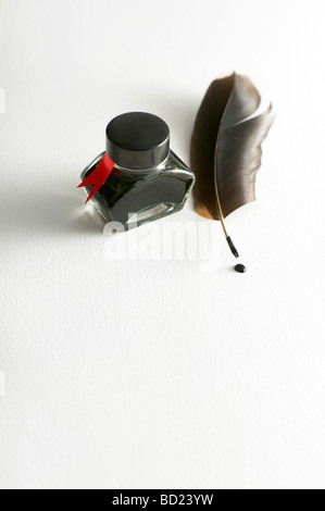 INK BOTTLE WITH QUILL PEN ON WHITE PAPER - Stock Photo