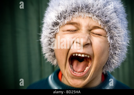 Close up of portrait of crazy kid screaming loudly - Stock Photo