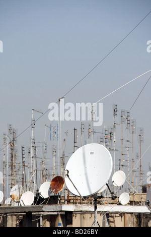 many tv aerials and satellite dishes on rooftops - Stock Photo
