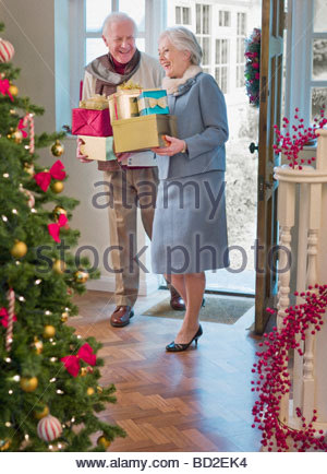 Couple entering house with Christmas gifts - Stock Photo