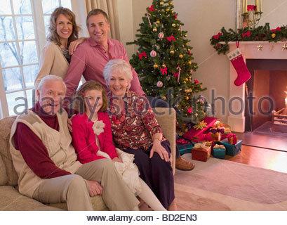 Multi-generation family sitting on sofa near Christmas tree - Stock Photo