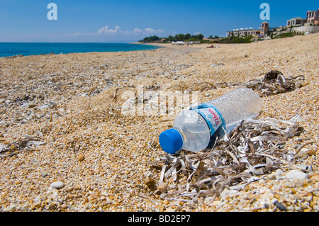 Plastic water bottle dropped as litter on beach at Skala on the Greek island of Kefalonia Greece GR - Stock Photo