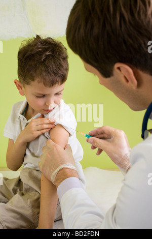 male doctor giving injection to a boy - Stock Photo