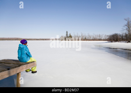 Woman Relaxing on Dock by Frozen Lake - Stock Photo