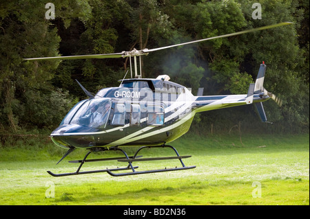 Helicopter landing in a field, UK. Helicopter tourism trip on a sight seeing flight, England. - Stock Photo