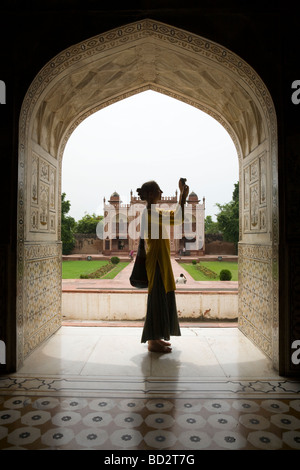 Western woman tourist photographing in an archway of Itmad-ud-Daulah's Tomb mausoleum. Agra. India. - Stock Photo