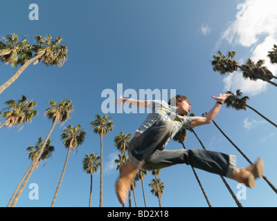 Man leaping in front of palm trees - Stock Photo