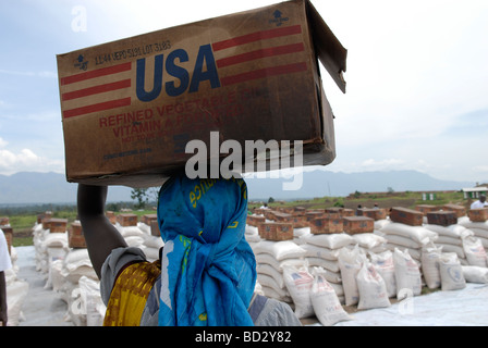 Man carrying box of refined vegetable oil donated by USAID at a World Food Programme distribution point in North - Stock Photo
