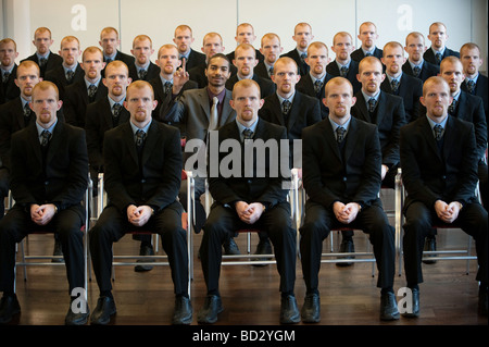 1 black surrounded by 25 white clones - Stock Photo