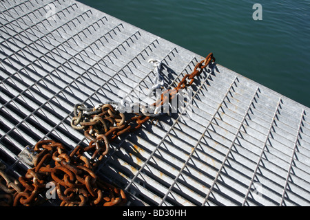 old rusty chain on metal pier in harbour by sea - Stock Photo