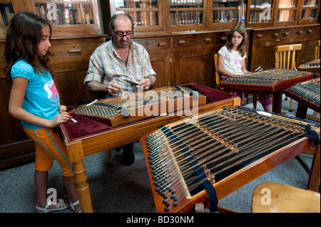 Greek children at music lesson learning to play traditional santouri stringed instrument in Agiassos on Lesvos Island - Stock Photo