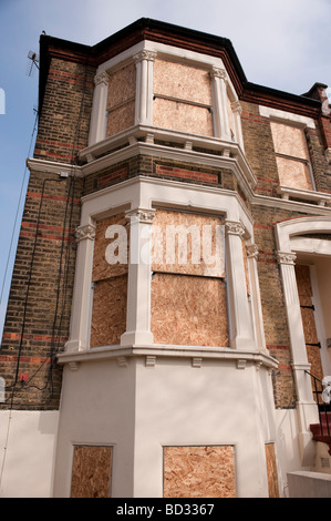 Boarded up semi-detached house in London - Stock Photo