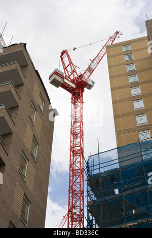 Red Construction Crane Between Two Buildings - Stock Photo