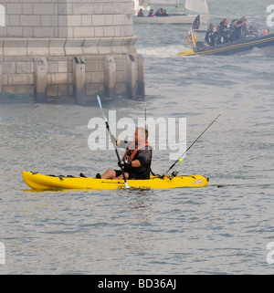 Fisherman paddling a ocean kayak through the entrance of Jubilee Haven the RYS at Cowes Isle of Wight England UK - Stock Photo