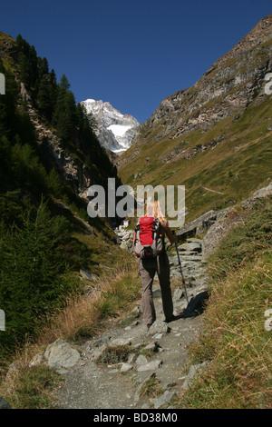 Female Hiker walking in direktion Wellenkuppe Zermatt Valais Switzerland - Stock Photo