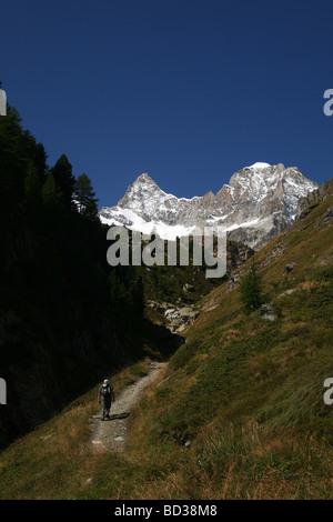 Hiker walking in direktion Ober Gabelhorn and Wellenkuppe Zermatt Valis Switzerland - Stock Photo