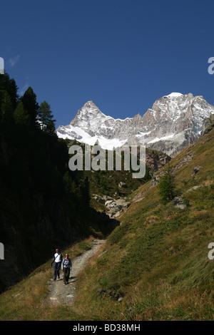 Hiker walking in direction Ober Gabelhorn and Wellenkuppe Zermatt Valis Switzerland - Stock Photo