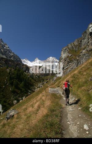 Female Hiker walking in direktion Ober Gabelhorn and Wellenkuppe Zermatt Valis Switzerland - Stock Photo
