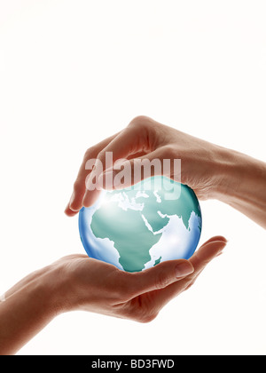 Two hands encircling glass globe isolated against white - Stock Photo