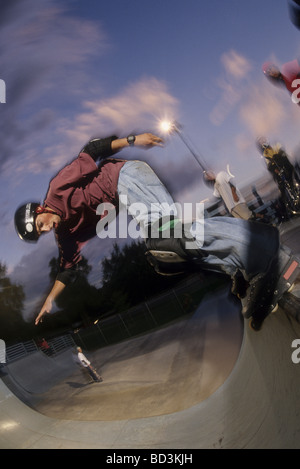 Inline skater hanging on the lip of the vert - Stock Photo