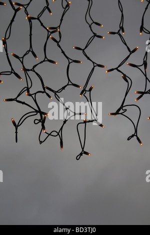 bundle of colourful christmas fairy lights hanging outside at night - Stock Photo